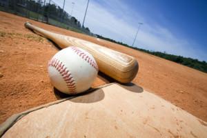 Baseball and bat on home plate of a ballpark